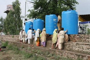 People collect water from Oxfam tanks in Nowshera, Pakistan, after the devastating 2010 floods. Flickr / Oxfam International